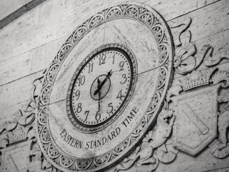 aged brick with clock and coat of arms